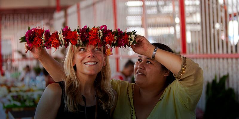 Woman at a market putting a flower headband on Cathryn