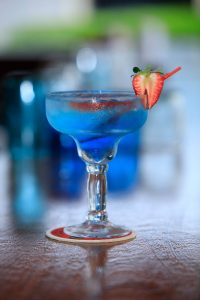 Blue tropical drink with strawberry garnish photographed in the Caribbean